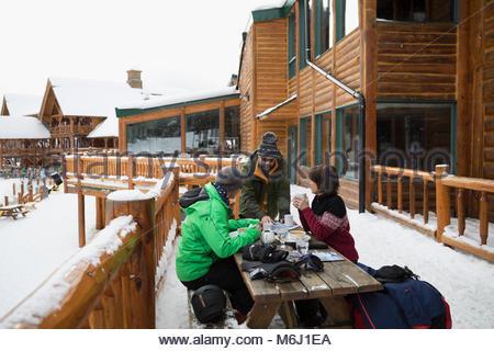 Mature skier friends enjoying apres-ski on snowy ski resort balcony - Stock Photo