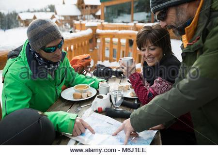 Mature friend skiers enjoying breakfast, preparing with map on ski resort balcony - Stock Photo