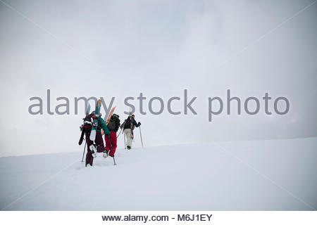 Female skier and snowboarder friends hiking up snow covered hill - Stock Photo