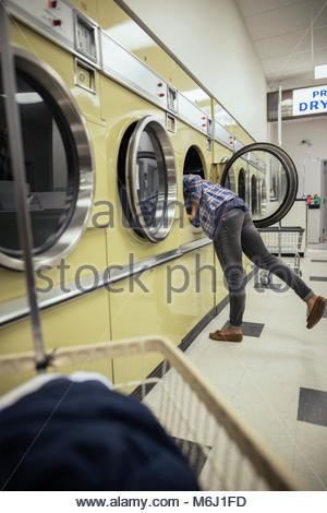 Young woman reaching in clothes dryer, doing laundry at laundromat - Stock Photo