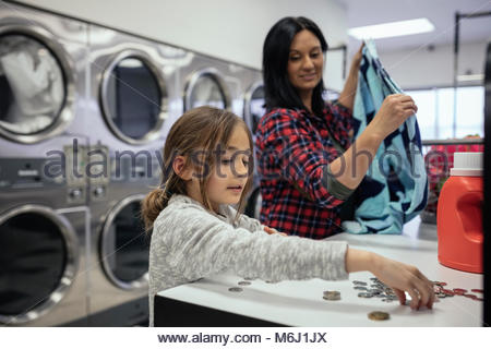 Daughter sorting coins, helping mother doing laundry at laundromat - Stock Photo