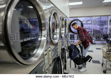 Young man with backpack doing laundry at laundromat - Stock Photo
