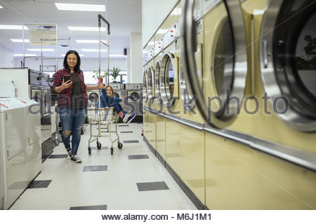 Mother and daughter with cart doing laundry at laundromat - Stock Photo