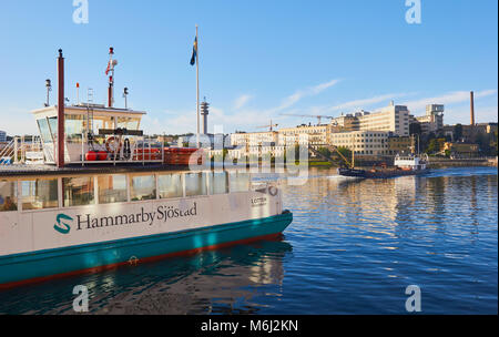 Ferry boat and barge, Hammarby Sjostad eco neighbourhood a pioneer in sustainable development, Hammarby Lake, Stockholm, - Stock Photo