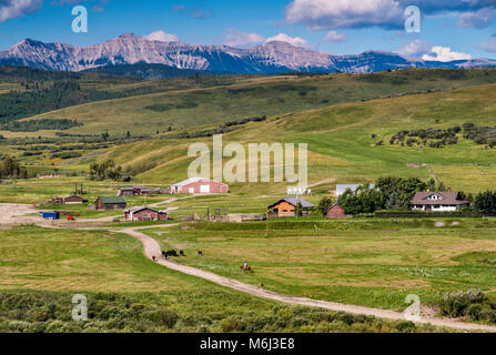 Ranch buildings in rolling foothills of the Canadian Rockies, visible in far distance, near Longview, Alberta, Canada - Stock Photo