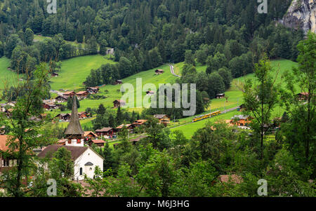 Picturesque mountain village Lauterbrunnen in the Bernese Alps. In the background the train from Kleine Scheidegg - Stock Photo
