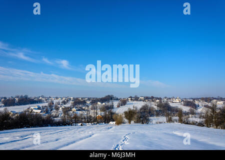 Amazing Ukrainian village with a charming sky in the snowy mountains, taken in the winter - Stock Photo