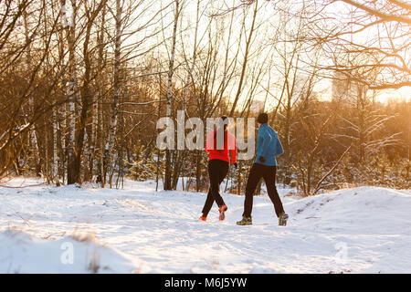 Photo from back of sportswoman and sportsman on morning run in winter - Stock Photo