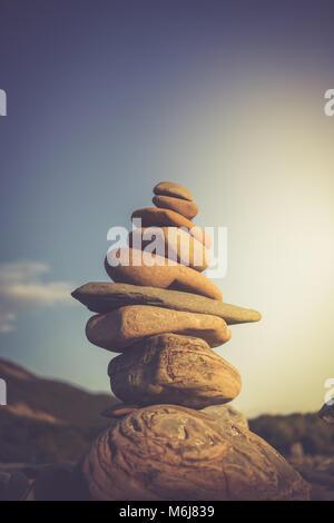 Stack of stones symbolizing Zen against sky. Toned image. - Stock Photo