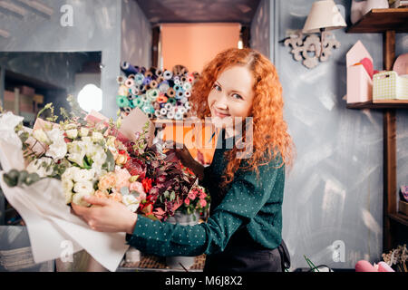 portrait of beautiful shop assistant taking two flower bouquets in flower shop - Stock Photo