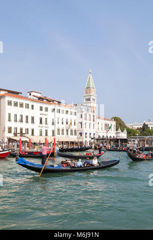 Several gondolas with tourists in the Grand Canal, Basino San Marco near the San Marco vaporetto stop, Venice, Italy - Stock Photo