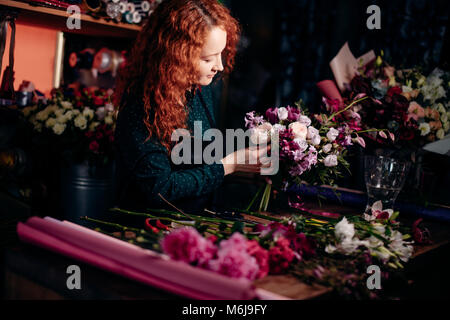 ginger assistant with curly hair making bouquet for Valentine's day indoor - Stock Photo