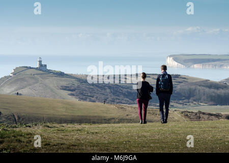 Couple walking along the Beachy Head coastal path, Belle Tout lighthouse  and Seven Sisters cliffs in the background - Stock Photo