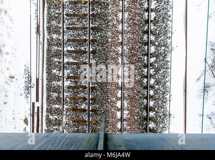 Cloudy winter day overhead view of UK Railroad in England from bridge. - Stock Photo