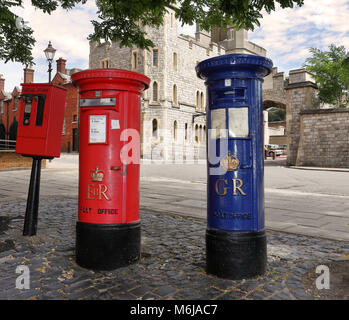 Vintage Red and Blue English Mail Boxes on a cobbled street with part of Windsor castle in the background - Stock Photo