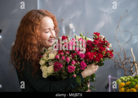 Female florist smelling flower bouquet in the flower shop - Stock Photo