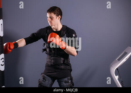 man in boxing gloves during training. boxer in suit of electric stimulation - Stock Photo