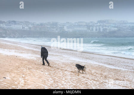 Snow falling as a man walks with his dog across Fistral beach in Newquay Cornwall. - Stock Photo