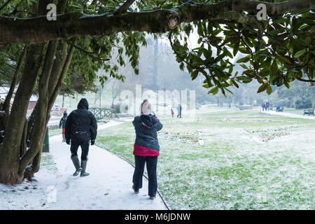 People walking through snow in Trenance Gardens in Newquay Cornwall. - Stock Photo