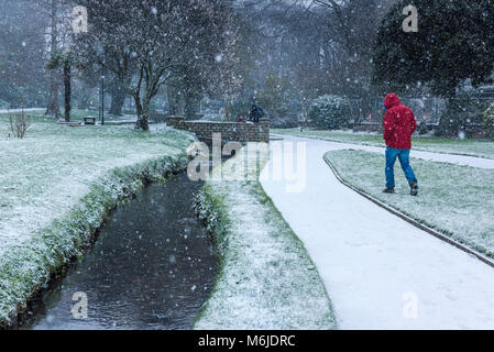 People walking through heavy snowfall in Trenance Gardens in Newquay Cornwall. - Stock Photo