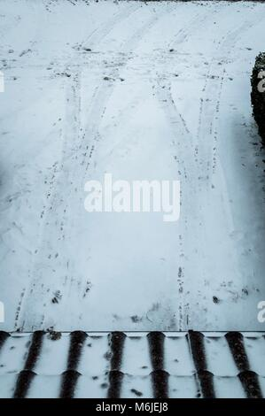 Tyre tracks from a car in the snow on a driveway - Stock Photo