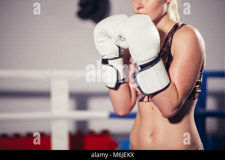 Female Boxer wearing gloves posing in boxing studio - Stock Photo