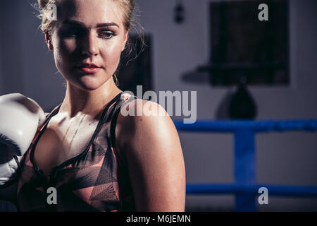 Female Boxer wearing gloves posing in boxing studio - Stock Photo