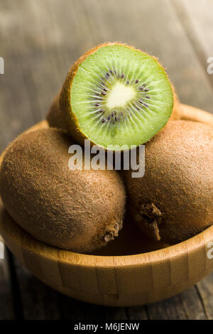 Halved kiwi fruit in bowl. - Stock Photo