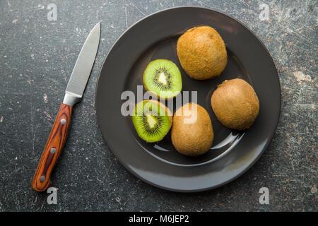 Halved kiwi fruit on plate. - Stock Photo