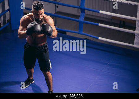 man boxing workout on ring. Caucasian male boxer in black gloves - Stock Photo
