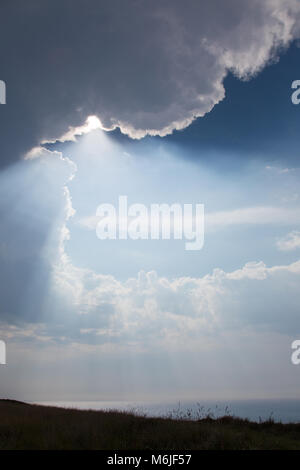 The sun peeks through a break in the clouds above Bailiwick of Guernsey, UK - Stock Photo