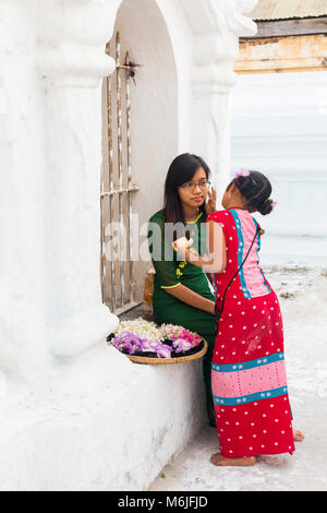 Girl applying thanaka on cheek of lady at Kuthodaw Pagoda, Mandalay, Myanmar (Burma), Asia in February - Stock Photo