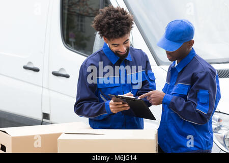 Delivery Man Writing On The Clipboard Over The Cardboard Boxes Standing By The Truck - Stock Photo