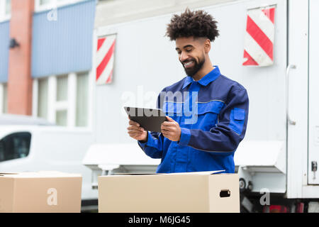 Smiling Delivery Man Standing Near The Van Checking His Order On Digital Tablet - Stock Photo