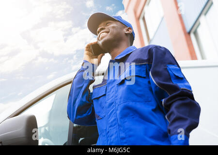 Low Angle View Of Happy Delivery Young Man Standing Near Van Talking On Cellphone - Stock Photo