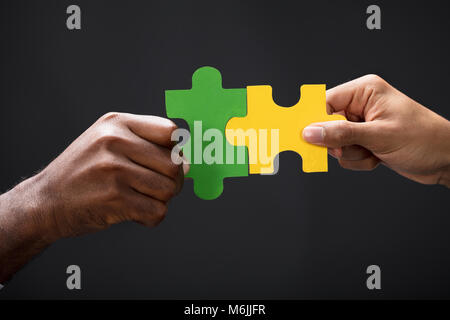 Close-up Of Business Partners Combining Two Puzzle Pieces On Black Background - Stock Photo