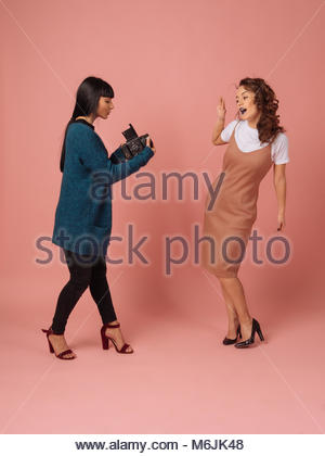 Girl photographer takes pictures of model on pink background in studio with retro film camera - Stock Photo