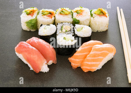 Plate of sushi rolls. Sushi set sashimi and sushi rolls served on wooden plate. Rolls with salmon, eel, tuna, avocado, - Stock Photo