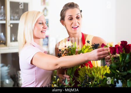 Flower shop sales woman giving advice to customer - Stock Photo