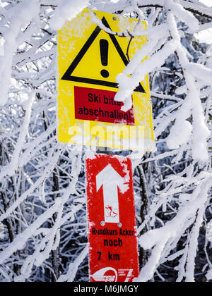 Warning sign on loipe, steep hill,  take off skis, Harz, Lower-Saxony, Germany - Stock Photo
