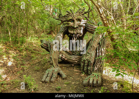 Woodland greenman sculpture setting in forest dappled with sun and shade at Renassiance Festival Muskogee Oklahoma - Stock Photo