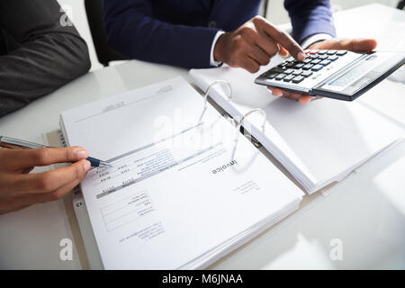 Two Businessman Calculating Bills Using Calculator At Workplace - Stock Photo