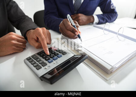 Close-up Of Two Accountants Calculating Tax Invoice Using Calculator On Desk In Office - Stock Photo
