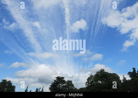 A bright blue sky with whispy streaks and puffs of clouds on a summer's day in Derbyshire, England, UK - Stock Photo