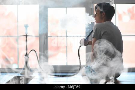 Man in sunglasses smoking a hookah - Stock Photo