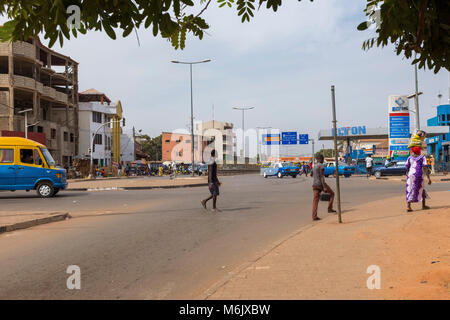 Bissau, Republic of Guinea-Bissau - January 28, 2018: Street scene in the city of Bissau, with people crossing a - Stock Photo