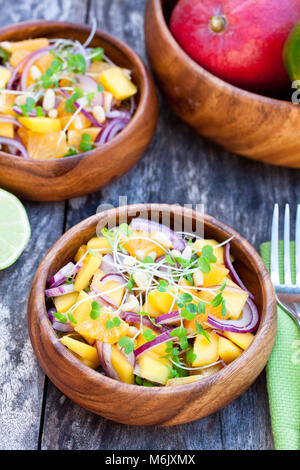 vegetarian  salad with mango oranges and red onion in the wooden plate - Stock Photo