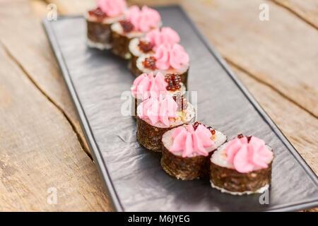 Tasty japanese sushi rolls on plate. - Stock Photo