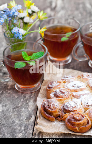 homemade  cinnamon buns with tea cups and bunch of wild flowers - Stock Photo