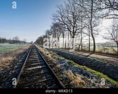 Railroad tracks of the OHE,  Osthannoversche Eisenbahnen, winter day, rural road, railway network, Lachtehausen, - Stock Photo